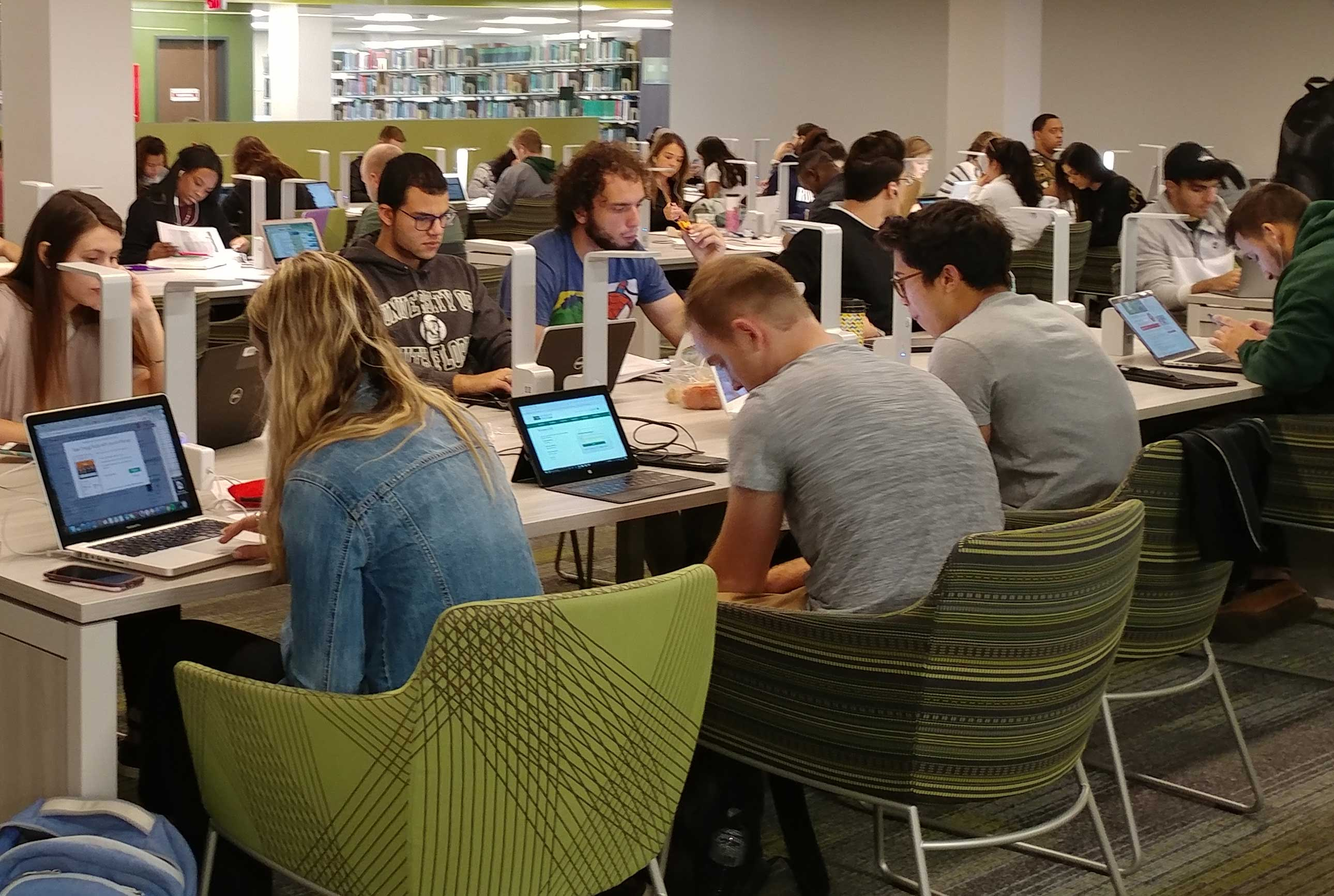 An image of students seated in the library using laptops